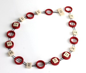 pendant with red plastic circles and white acrylic squares threaded together